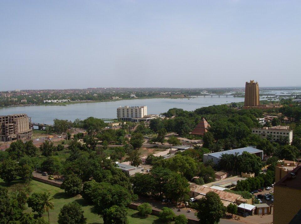 Na zdjęciu lotniczym miasto nad szeroką rzeką, teren zabudowany zdużą ilością zieleni.