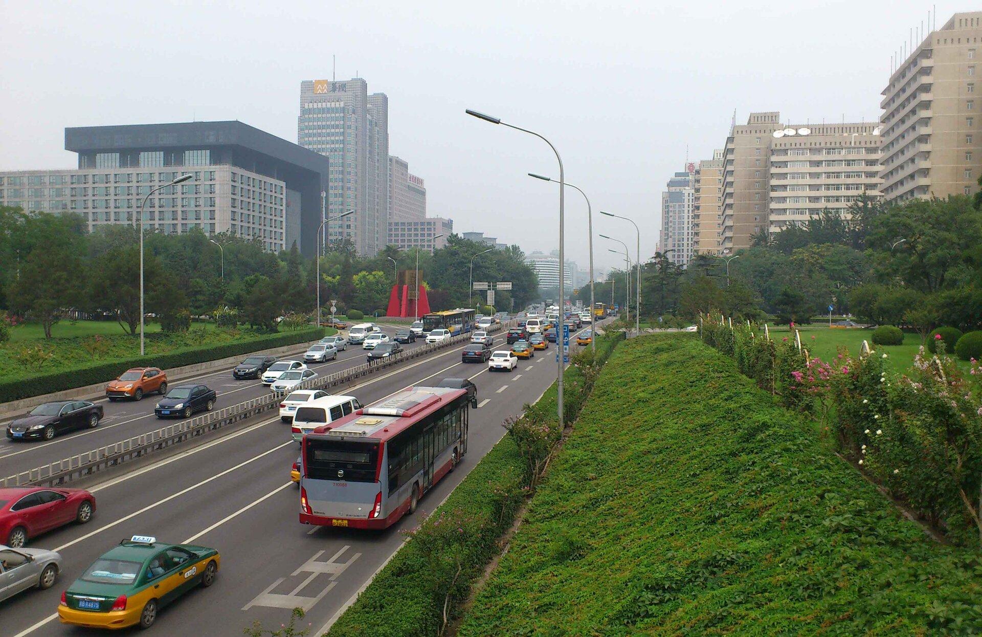 Na zdjęciu wielkiego miasta, szerokie wielopasmowe ulice, wysokie budynki. Dużo zieleni.