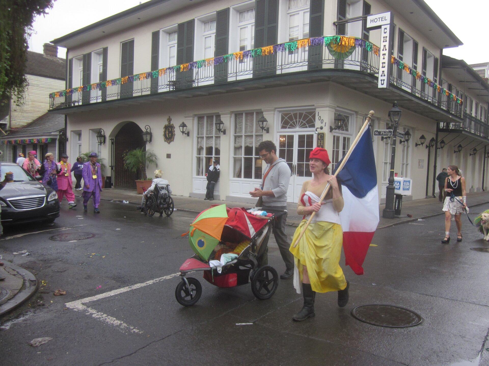 Zdjęcie współczesne, wcentrum mężczyzna zwózkiem dziecięcym iidąca obok niego kobieta wstroju marsylianki zfrancuską flaga, wtle budynek.