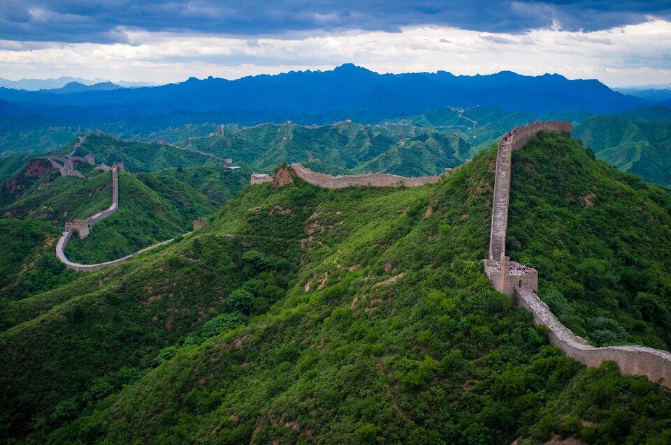 Na zdjęciu Wielki Mur Chiński, przebiegający po szczytowych partiach pasma górskiego porośniętego lasami, wieże sygnalizacyjne. Na murze turyści.