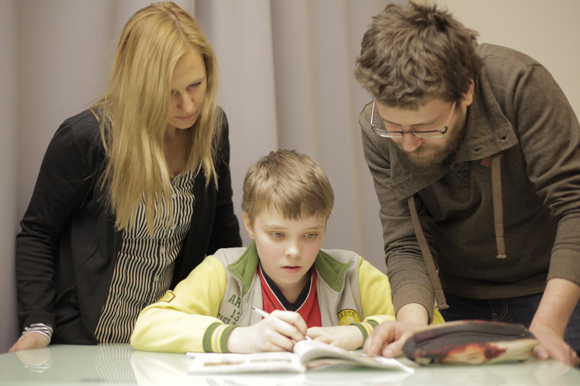 Fotografia prezentuje chłopca siedzącego przy stole iodrabiającego lekcje. Nad nim pochylają się rodzice pomagający odrabiać zadania.