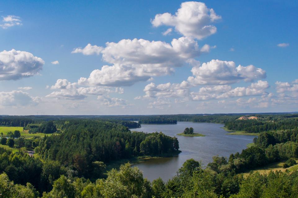 Galeria zdjęć ukazujących przyrodę pojezierzy. Fotografia ukazuje jeziora Pojezierza Mazurskiego otoczone drzewami liściastymi.