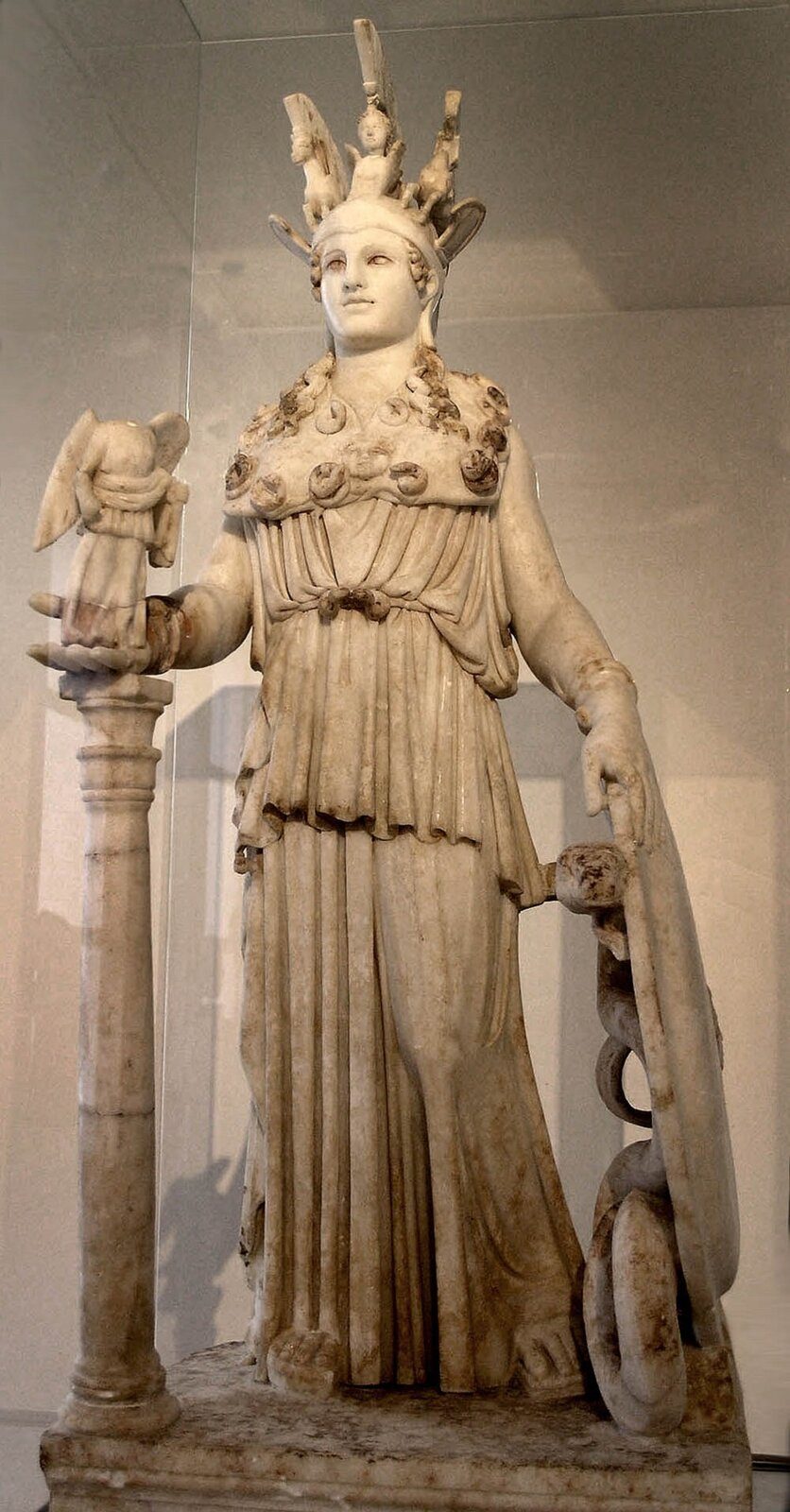 """Ilustracja przedstawia rzeźbę Fidiasza pt. """"Atena Partenos"""". Na fotografii ukazany jest posąg stojącej Ateny whełmie idługim peplosie, zegidą ifigurą Nike na prawej dłoni oraz włócznią itarczą przy lewym boku. Szczyt jej hełmu zdobił gryf między dwoma sfinksami, egidę – głowa Meduzy, tarczę – amazonomachia igigantomachia, sandały – centauromachia."""