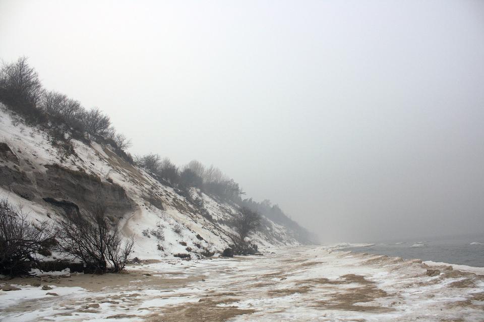 Galeria prezentuje rozmaitość terenów nizinnych Polski. Pierwsze zdjęcie przedstawia pobrzeże Bałtyku zimą. Widoczny wysoki brzeg zwąskim pasem plaży.