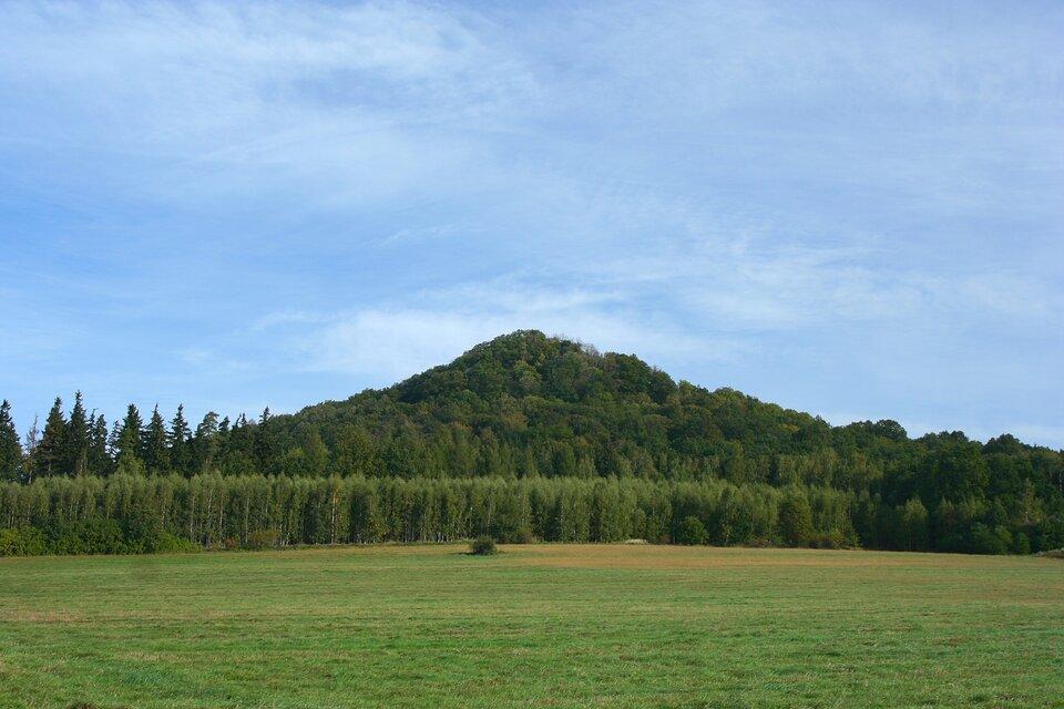 Na zdjęciu wzniesienie wkształcie stożka. Wzniesienie odość stromych zboczach, zwyraźnie podkreślonym wierzchołkiem, porośnięte lasem.