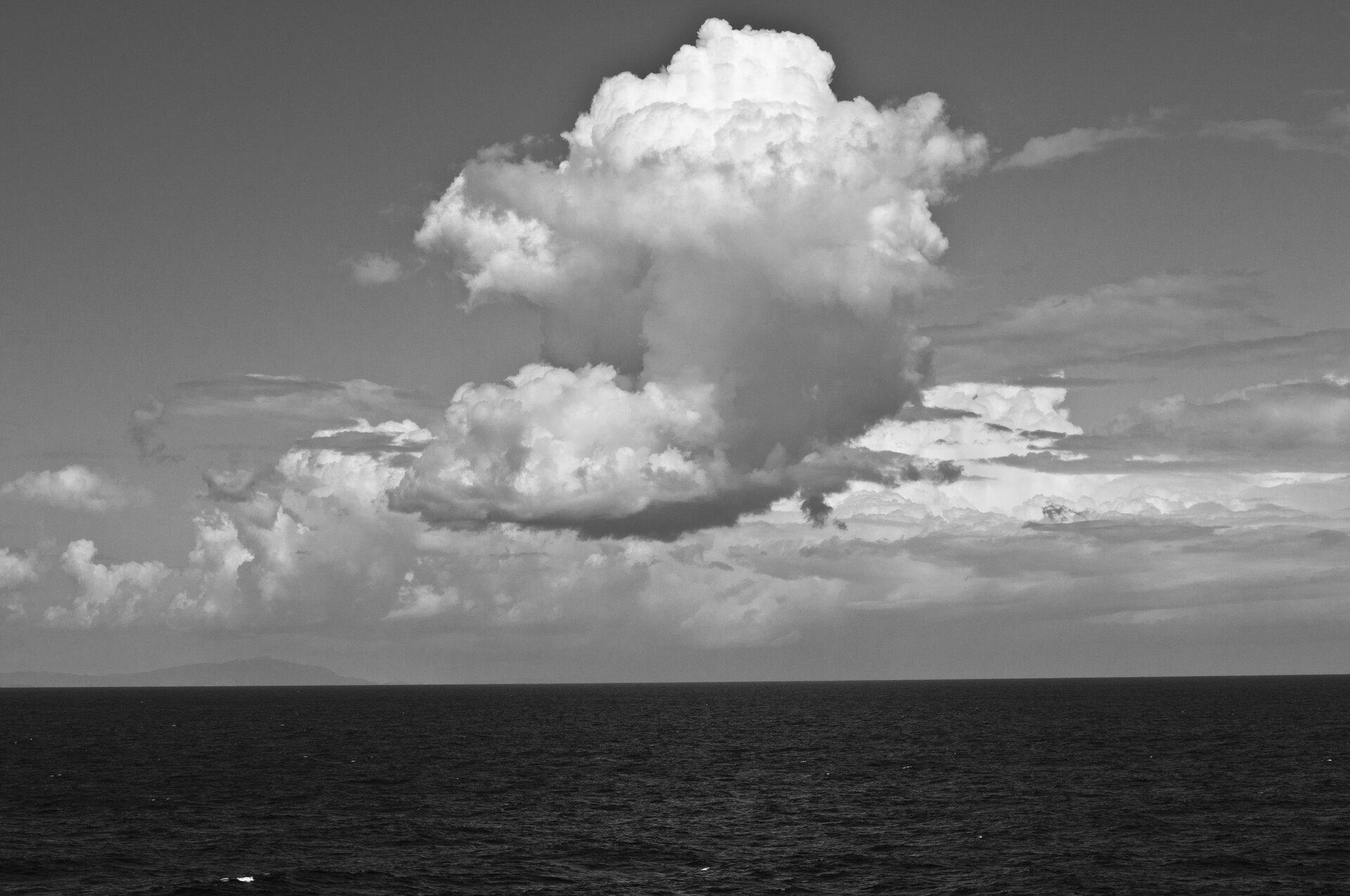 """Ilustracja przedstawia fotografię """"Niebo II"""" autorstwa Anny Koli. Czarno-białe zdjęcie ukazuje pejzaż morski. Wcentrum , na tle nieba unosi się duży obłok poszarpanej, białej chmury. Poniżej znajduje się wąski pas ciemnego, płaskiego morza. Nad horyzontem rysuje się szary kształt lądu. Praca skomponowana jest statycznie."""