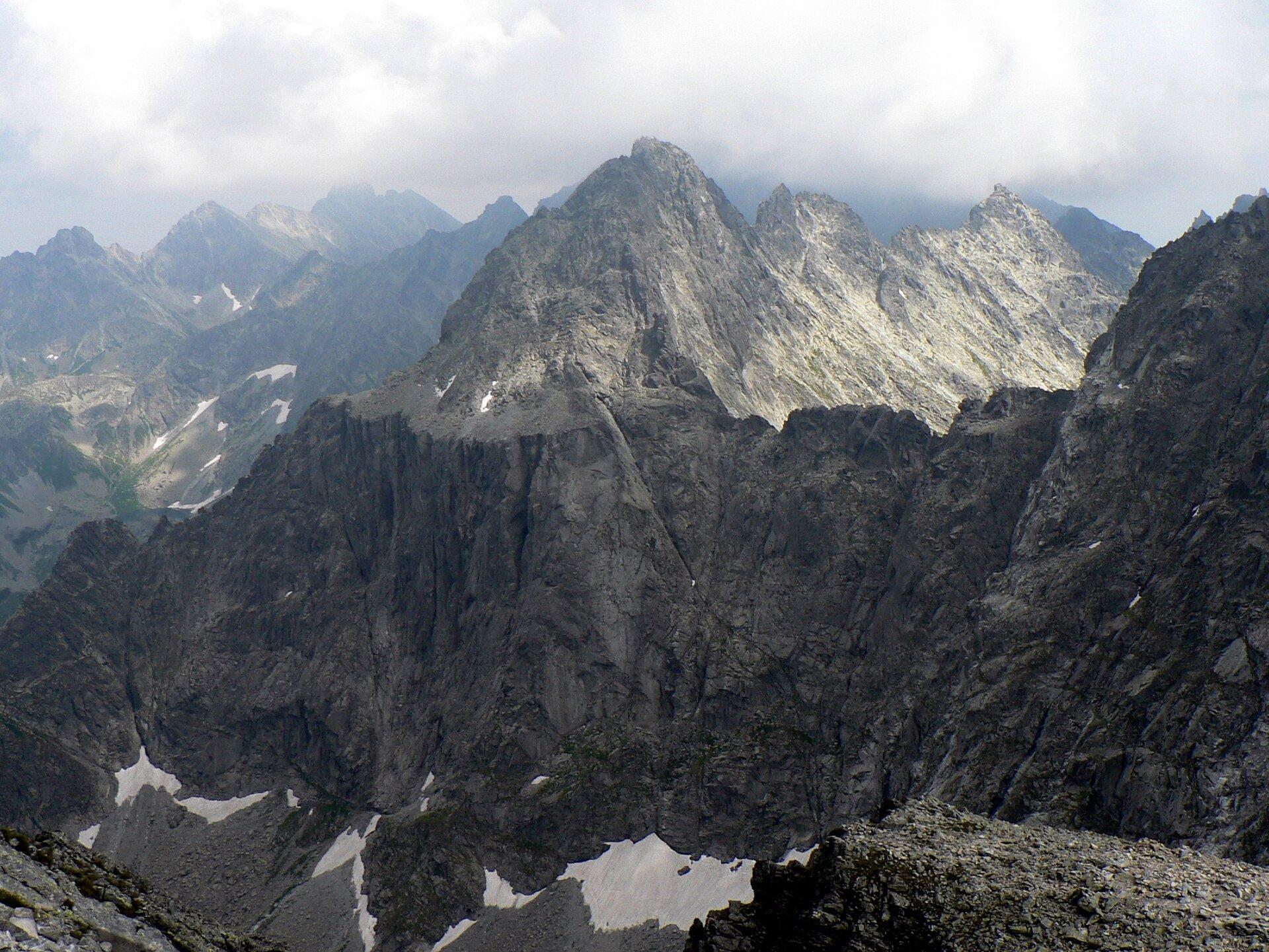 Na zdjęciu bardzo wysokie ostrokrawędziste, szpiczaste szczyty górskie pozbawione roślinności.