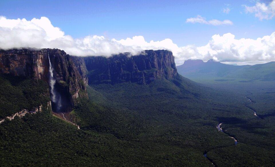 Na zdjęciu wąska strużka wody spadająca zbardzo wysokiego stromego stoku. Wdole gęsta roślinność, wdnie bardzo szerokiej doliny stosunkowo wąska rzeka.
