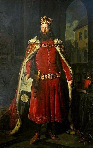 Obraz przedstawiający portret Kazimierza Wielkiego. Ubrany wodświętną szatę zkoroną na głowie. Wręku trzyma księgę iją prezentuje, do pasa przywiązany ma sztylet.