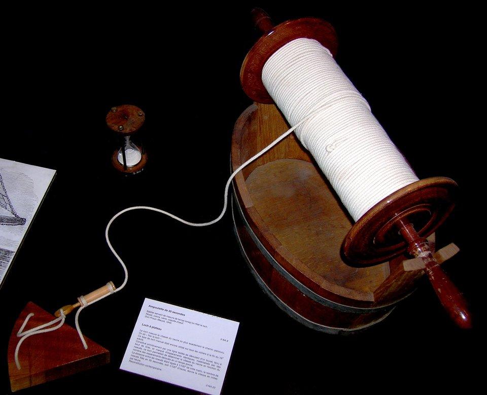 Na zdjeciu przedstawiony jest log, czyli urządzenie służace do określeniapręsdkości zjaka porusza się statek. Jestto trójkątna deska, do każdego jej rogu przymocowano trzy końce rozplecionej liny.