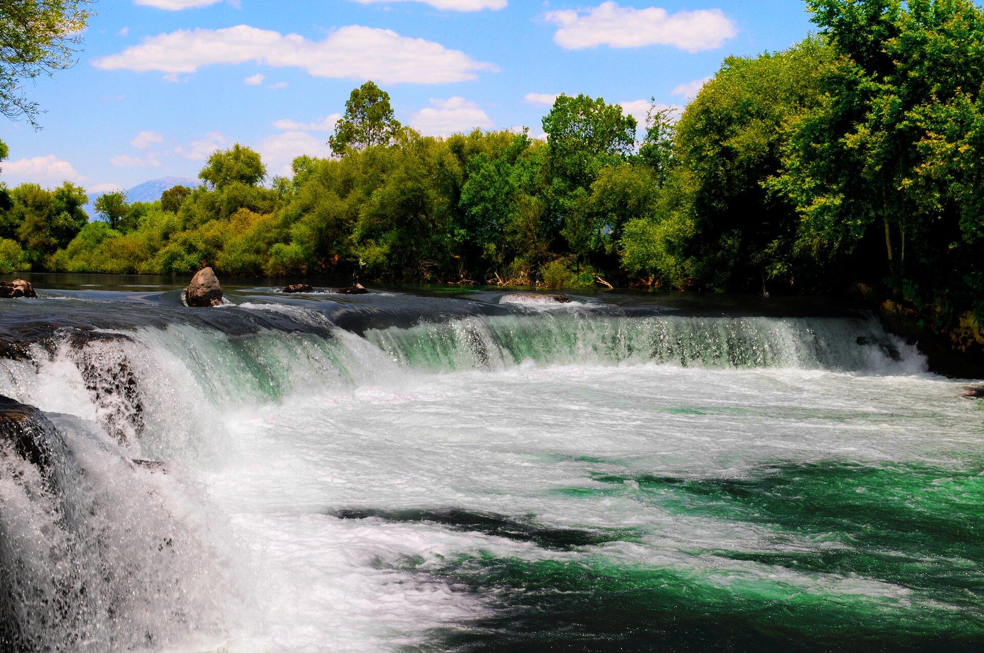 Zdjęcie przedstawiające fragment rzeki otoczonej drzewami, przeciętej przez szeroki istosunkowo niski wodospad lub duży próg. Ilustracja stanu skupienia ciekłego.