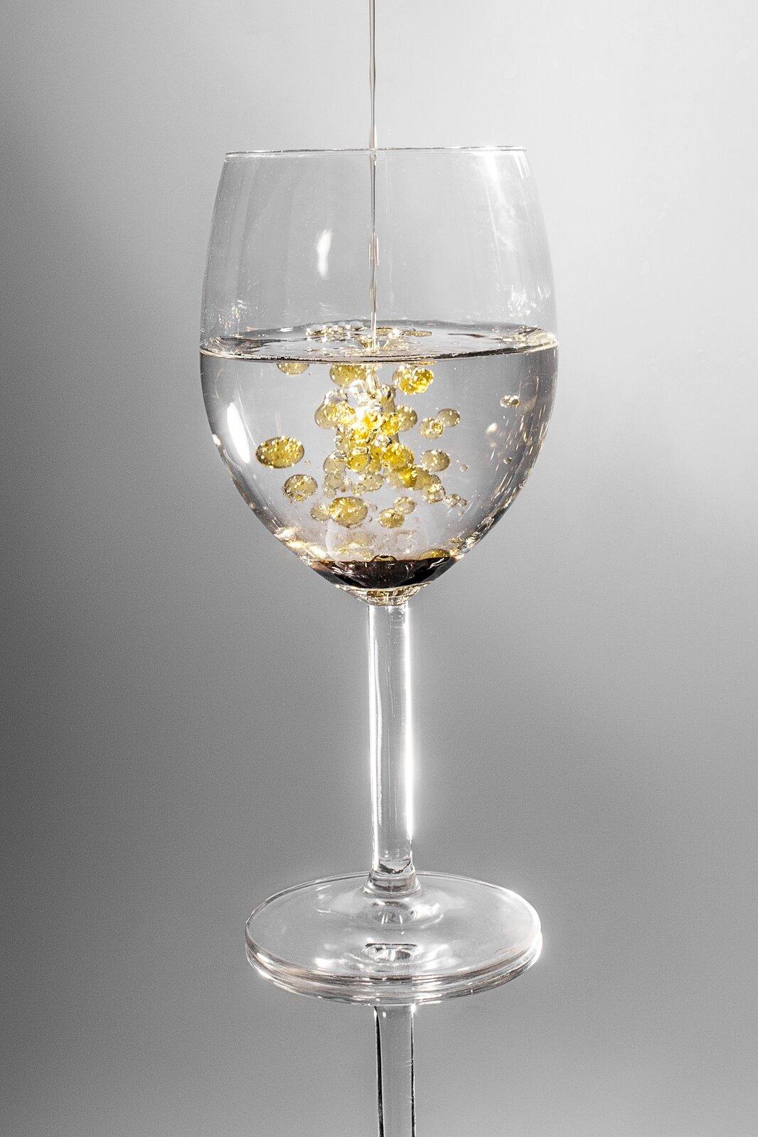Zdjęcie kieliszka zwodą do której wlewana jest wąska struga oleju. Olej wwodzie tworzy wyraźne złote krople.