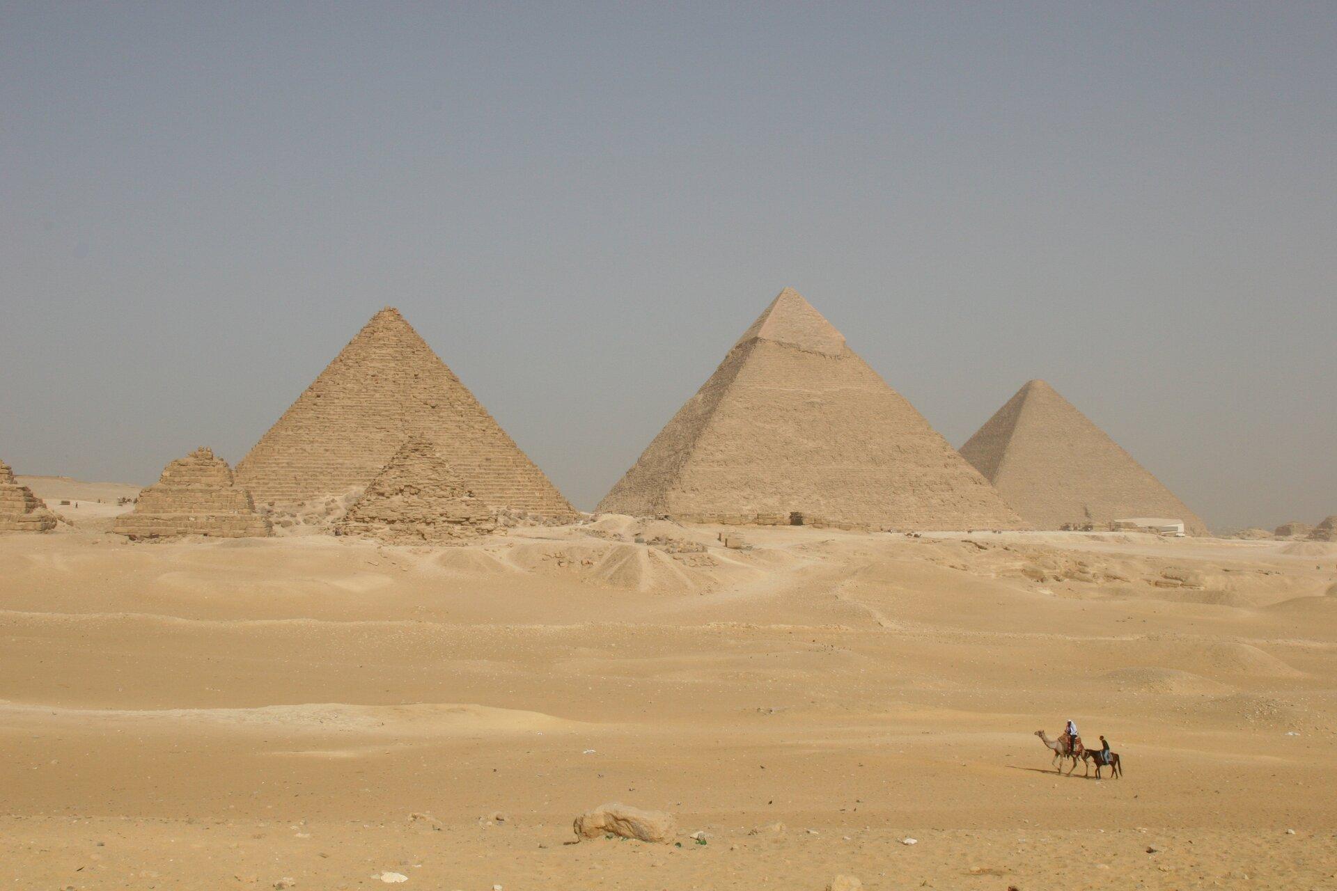 Fotografia trzecia prezentuje piramidy na pustyni.