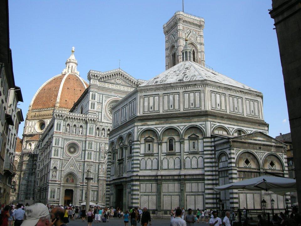 """Florencja – katedra – widok ogólny zbaptysterium na pierwszym planie, dzwonnicą, awtle katedrą ikopułą.Katedrępw. Santa Maria del Fiore (Świętej Marii Kwietnej) zaczęto wznosić w1296 r. ibudowa jej trwa nieprzerwanie do dnia dzisiejszego. Główny korpus nawy głównej ukończono wXIV w. (1295-1379 r. – szerokość 38 m, długość 153 m); kopułę wstanie surowym wzniesiono wlatach 1418-1443 (wysokość 107 m, średnica kopuły 45 m); stojącą obok dzwonnicę rozpoczęto budować w1298 r., ajej dach zwieńczono w1359 r. (wysokość 85 m). Fasadę rozpoczęto wXIII w., ale w1588 r. rozebrano ją jako """"niemodną"""" irozpoczęto jej realizację od nowa. Ostatnie prace przy fasadzie miały miejsce wXIX w.; obecnie trwają prace przy wykończeniu kopuły.Na zdjęciu widać m.in. fragment ukończonej wXIX w. fasady głównej; przy kopule nad okrągłym oknem (nazywanym """"okulusem"""") widać fragment ciągle jeszcze nie skończonego gzymsu wieńczącego. Florencja – katedra – widok ogólny zbaptysterium na pierwszym planie, dzwonnicą, awtle katedrą ikopułą.Katedrępw. Santa Maria del Fiore (Świętej Marii Kwietnej) zaczęto wznosić w1296 r. ibudowa jej trwa nieprzerwanie do dnia dzisiejszego. Główny korpus nawy głównej ukończono wXIV w. (1295-1379 r. – szerokość 38 m, długość 153 m); kopułę wstanie surowym wzniesiono wlatach 1418-1443 (wysokość 107 m, średnica kopuły 45 m); stojącą obok dzwonnicę rozpoczęto budować w1298 r., ajej dach zwieńczono w1359 r. (wysokość 85 m). Fasadę rozpoczęto wXIII w., ale w1588 r. rozebrano ją jako """"niemodną"""" irozpoczęto jej realizację od nowa. Ostatnie prace przy fasadzie miały miejsce wXIX w.; obecnie trwają prace przy wykończeniu kopuły.Na zdjęciu widać m.in. fragment ukończonej wXIX w. fasady głównej; przy kopule nad okrągłym oknem (nazywanym """"okulusem"""") widać fragment ciągle jeszcze nie skończonego gzymsu wieńczącego. Źródło: Sailko, Wikimedia Commons, licencja: CC BY-SA 3.0."""