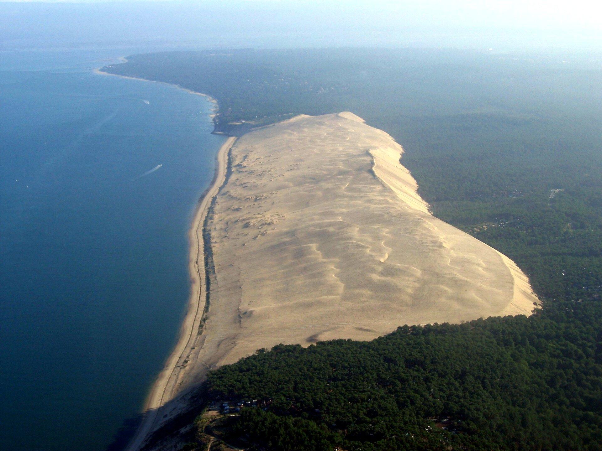Na zdjęciu wydma paraboliczna na brzegu morza. Morze zlewej strony. Zprawej strony olbrzymie połacie lasu.