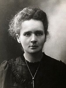 Czarno-białe zdjęcie portretowe Marii Skłodowskiej-Curie. Kobieta zwrócona twarzą wkierunku obserwatora. Ma długie włosy wkolorze ciemny blond. Fryzura lekko pofalowana, zaczesana do tyłu. Wysokie czoło. Brwi ciemne, gęste. Oczy duże. Nos mały. Usta wąskie. Twarz pociągła, bez zmarszczek. Uszy małe. Kobieta ubrana wczarną sukienkę. Wokół dekoltu ozdobne drobne marszczenia materiału.