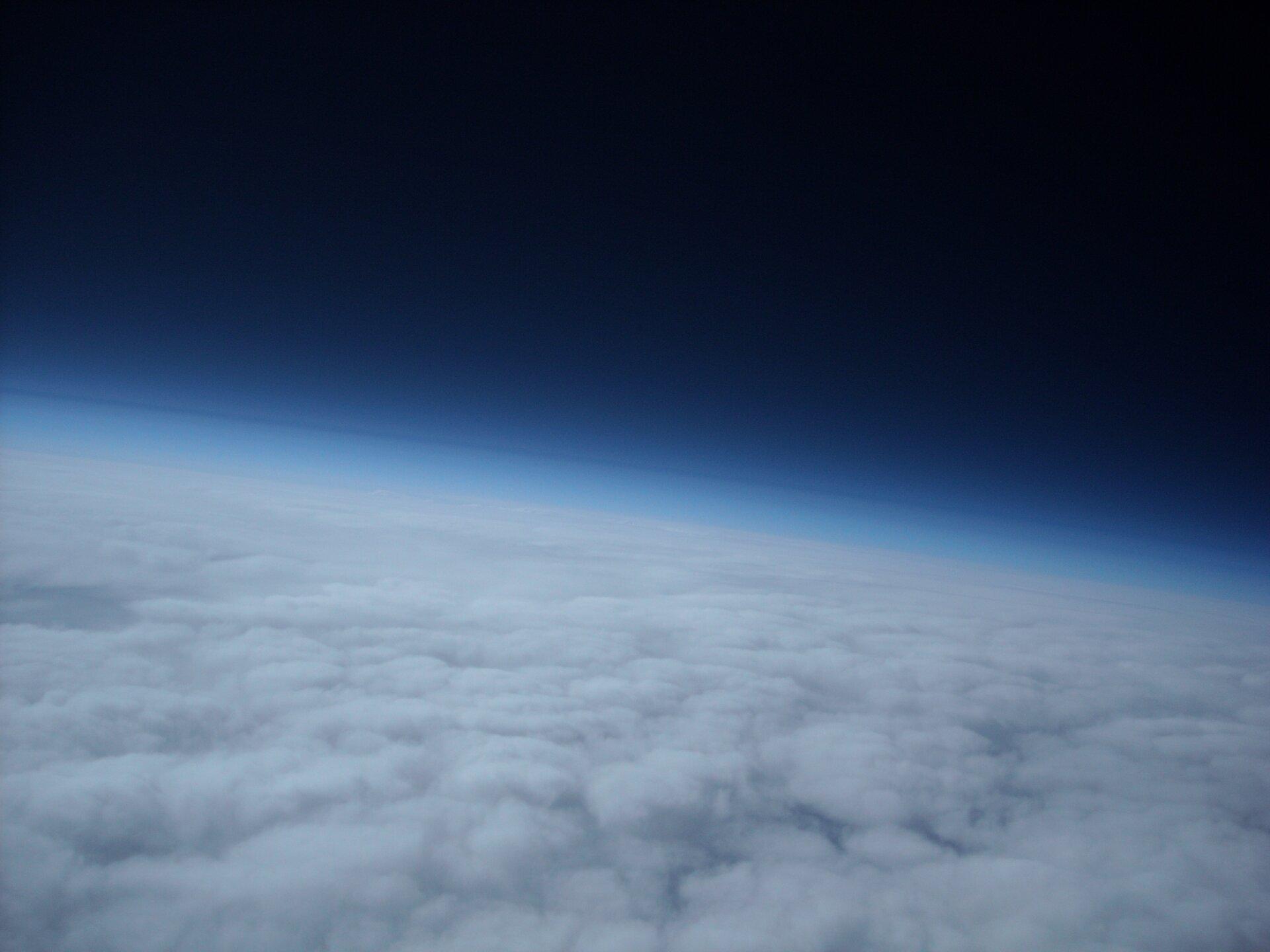Zdjęcie przedstawia atmosferę ziemską. Na zdjęciu widoczna jest planeta Ziemia zkosmosu?. Jest ona otoczona jasną/jasnoniebieską? gazową powłoką.