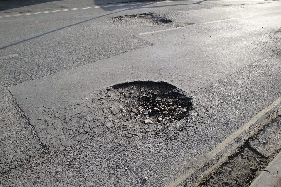 Fotografia przedstawia podziurawiony asfalt.