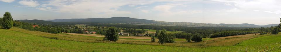 Druga fotografia , to krajobraz Gór Świętokrzyskich, widoczny teren falisty porośnięty trawą.