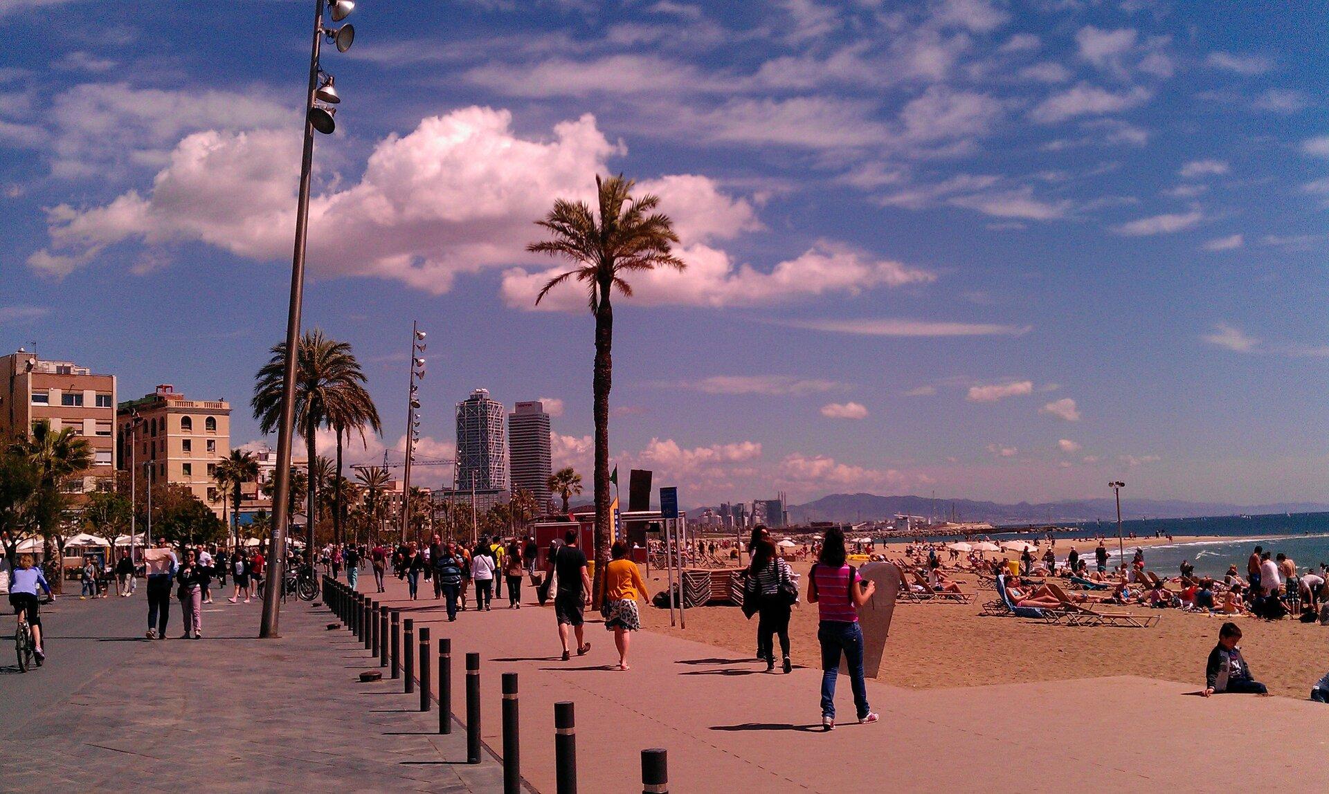 Galeria fotografii prezentująca ciekawe miejsca nad Morzem ŚródziemnymFotografia pierwsza prezentuje plażę przy promenadzie nad morzem. Na plaży ipromenadzie widocznych wiele osób. Wtle wysokie budynki.