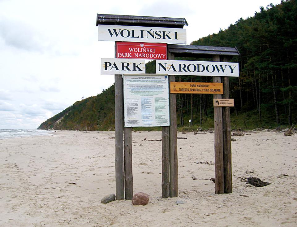 Fotografia prezentuje tablice informacyjne umieszczone na palach znajdujących się na plaży nadmorskiej