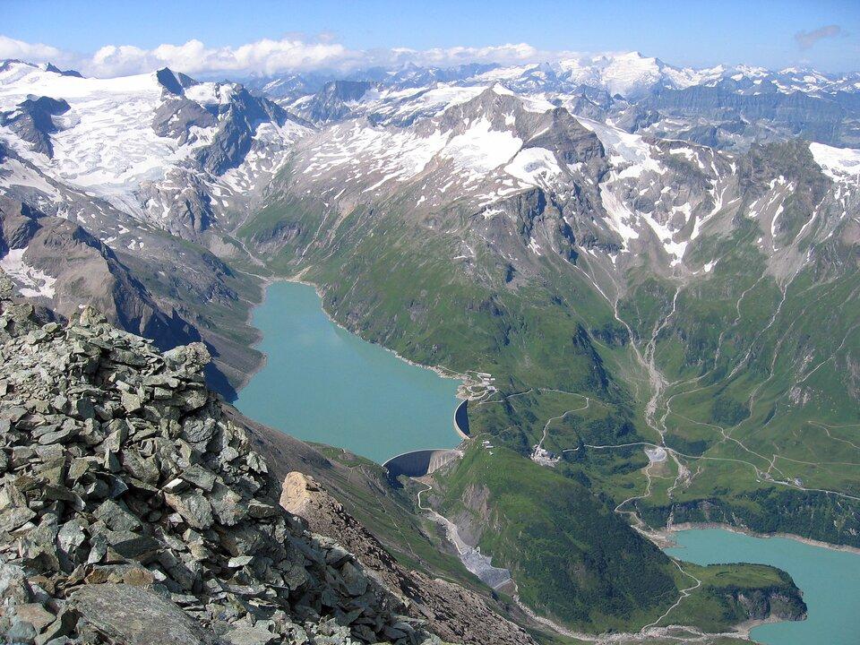 Na zdjęciu lotniczym dwie betonowe zapory na jeziorze położonym wśród gór. Skaliste szczyty pozbawione roślinności, ośnieżone, niżej porośnięte, wdolinach zielono. Zprawej strony drugie jezioro, dużo niżej położone.