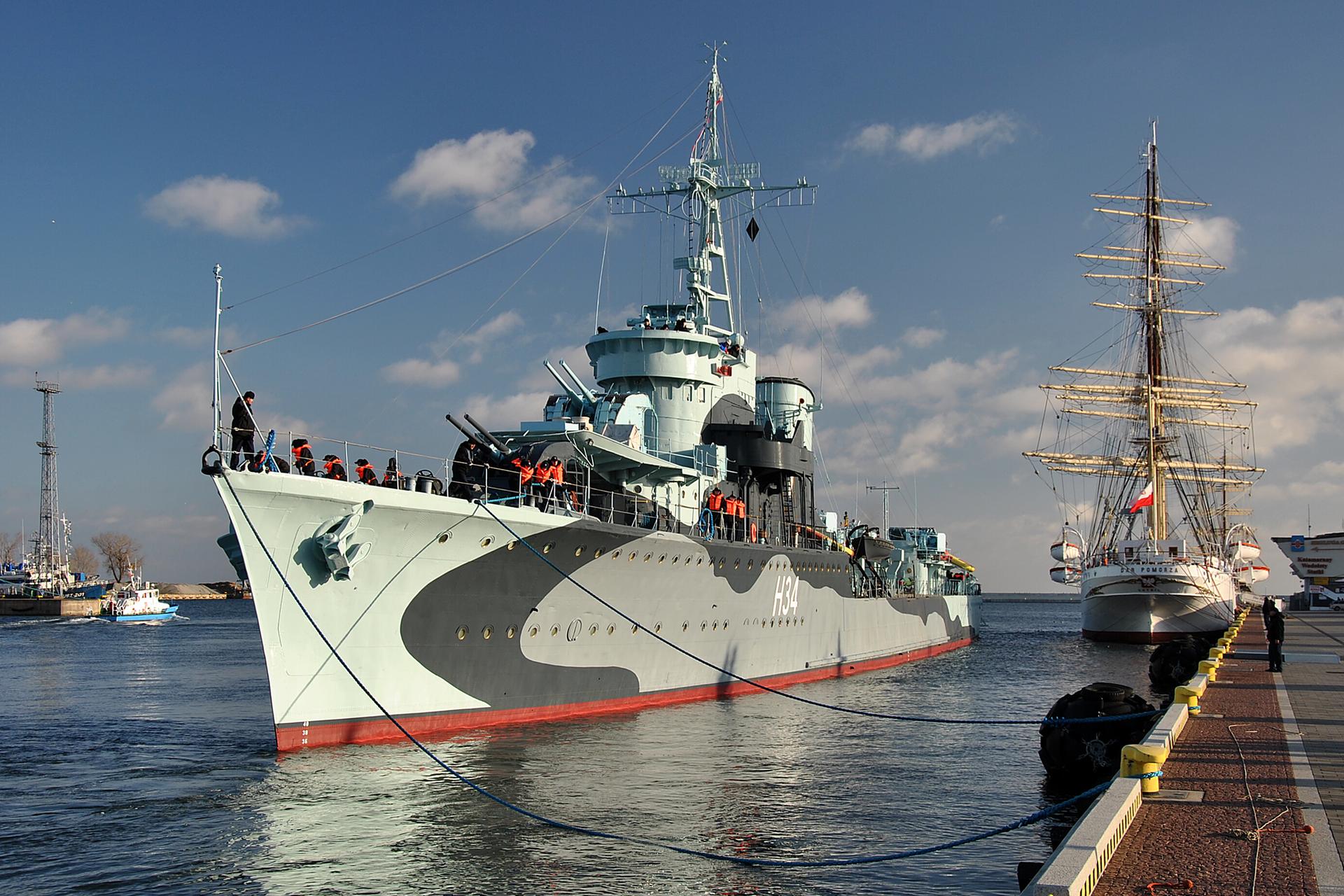 """Zdjęcie przedstawiające statek-muzeum """"Dar Pomorza"""". Biały statek stoi przycumowany do nabrzeża."""