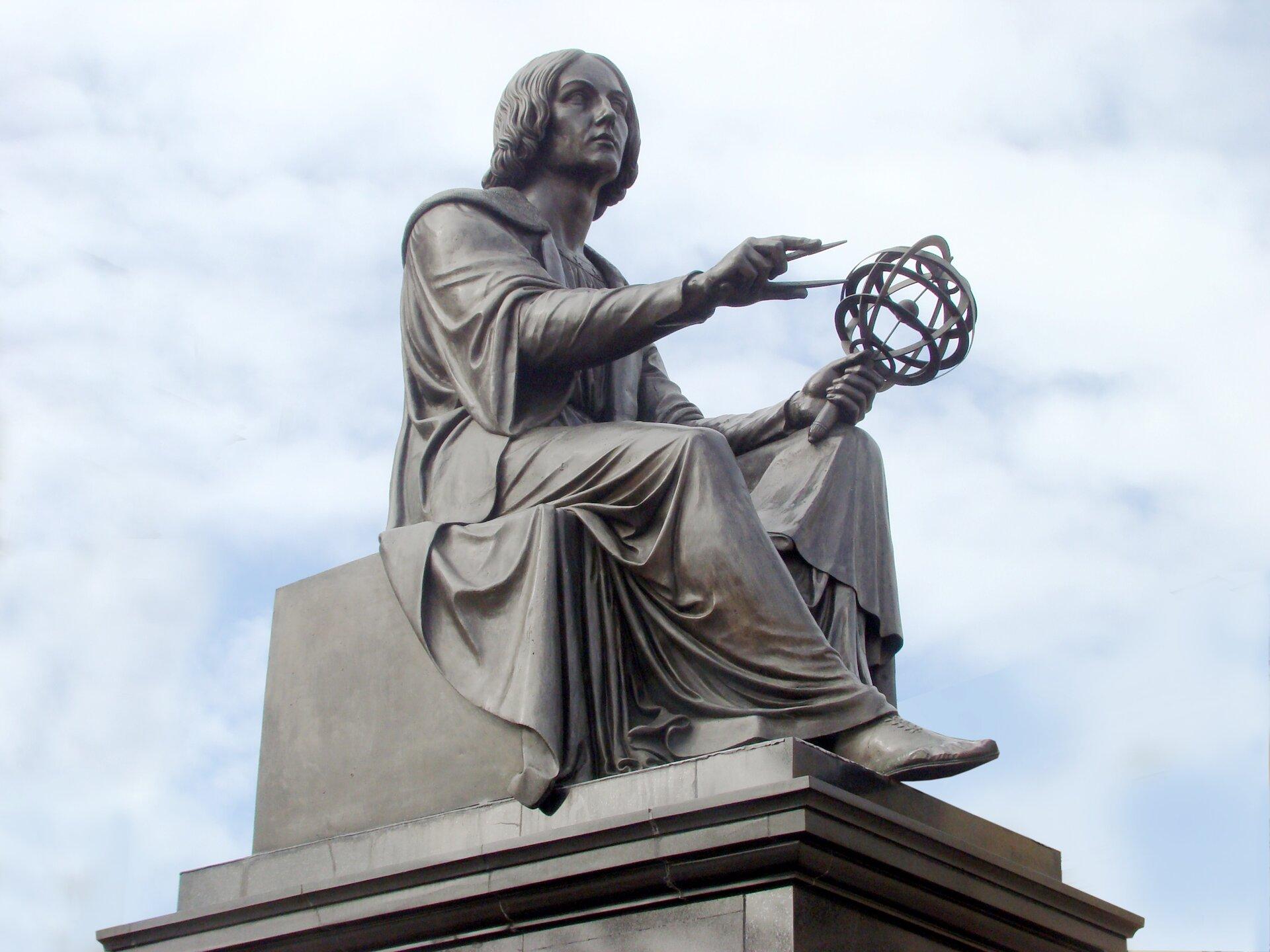 """Pomnik Kopernika wWarszawie W1822 odsłonięto pomnik Kopernika odlany wg projektu znanego duńskiego rzeźbiarza Thorvaldsena. Ufundowany został przez Stanisława Staszica, aodsłonięty przez innego wielkiego działacza oświeceniowego, J.U. Niemcewicza. Wczasie II wojny światowej polski napis na cokole """"Mikołajowi Kopernikowi rodacy"""" Niemcy zastąpili napisem """"Dem Grossen Deutschen Astronomen"""" (Wielkiemu niemieckiemu astronomowi). Źródło: Szczebrzeszynski, Pomnik Kopernika wWarszawie, 2010, fotografia, domena publiczna."""