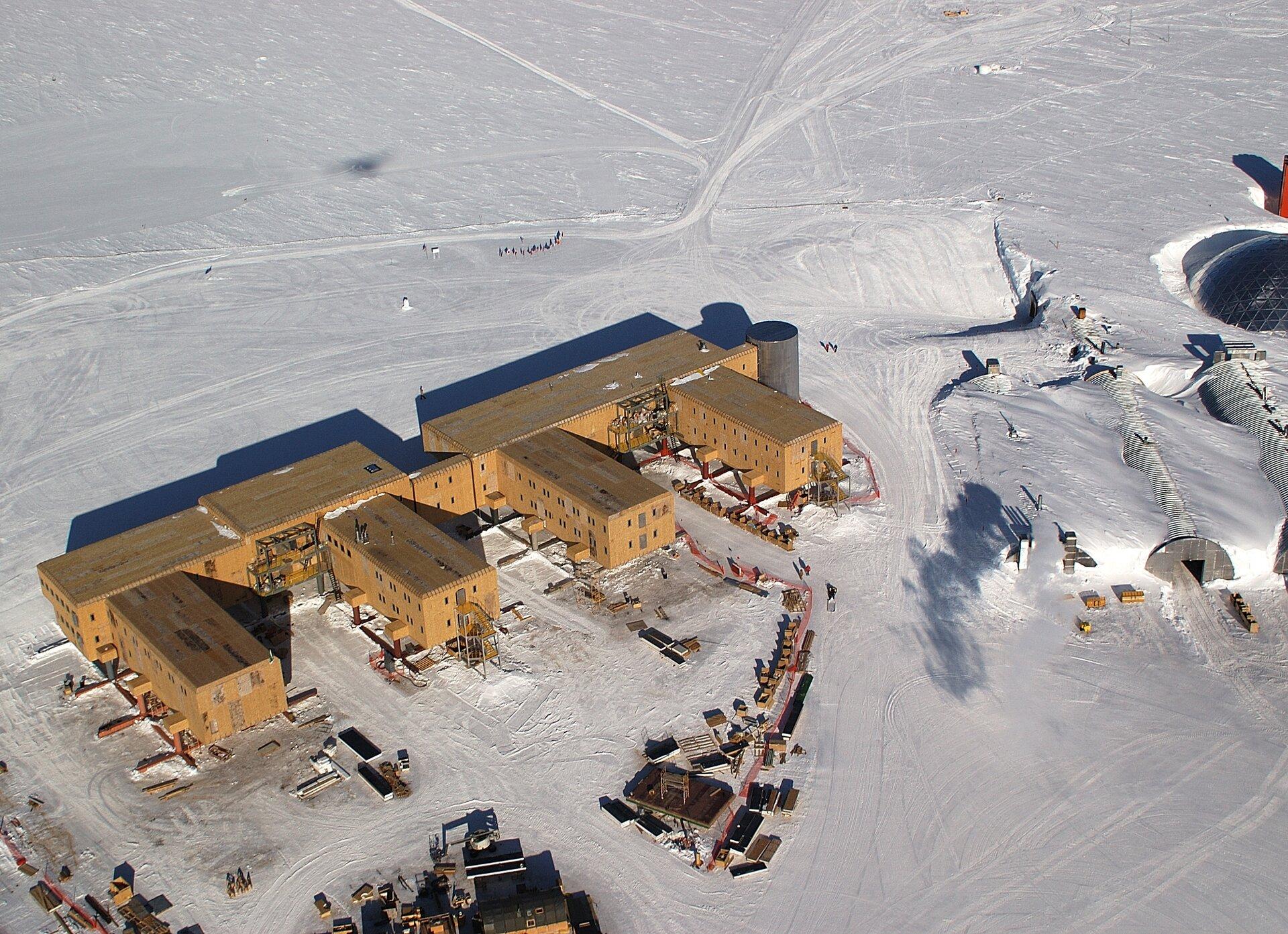 Na zdjęciu lotniczym kompleks kilku jednopiętrowych budynków na ośnieżonym terenie. Zprawej strony trzy zabudowania okształcie półokrągłych tuneli przysypane śniegiem po dach.