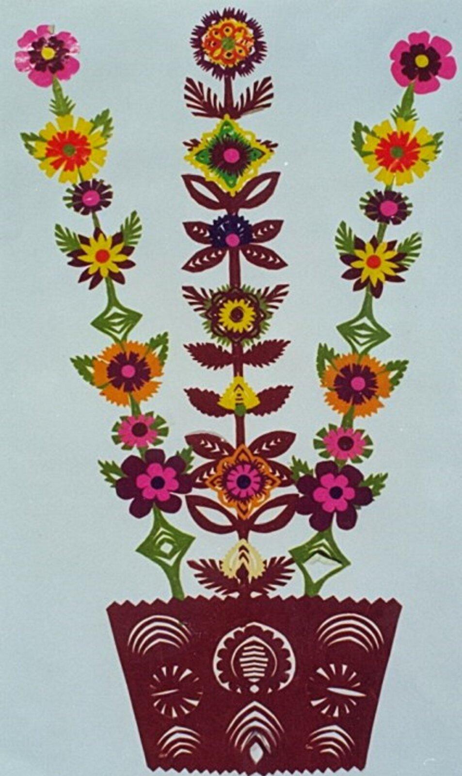 Ilustracja przedstawia sieradzką wierzbę. Jest to kolorowy wzór wycinanki przedstawiający kwiaty wdoniczce. Widzimy na nim zdobioną doniczkę, zktórej wyrastają trzy łodygi. Na łodygach na całej długości są kolorowe kwiaty. Dwie skrajne łodygi są takie same ale różnią się kwiatami od łodygi środkowej. Wzór przedstawiony jest na jasnym tle.