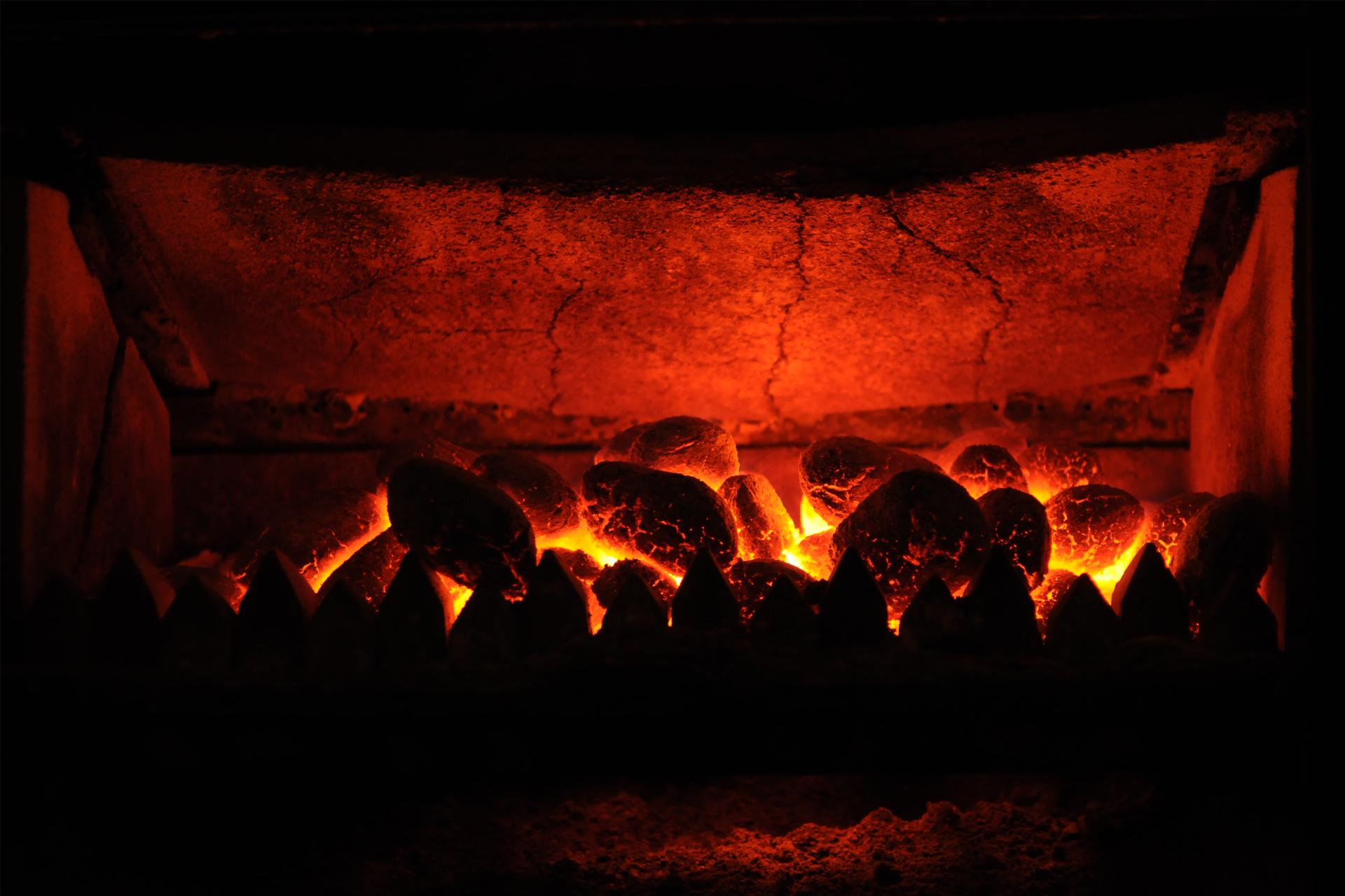 Zdjęcie przedstawia rozżarzone kawałki węgla palącego się wpiecu czerwonym płomieniem.