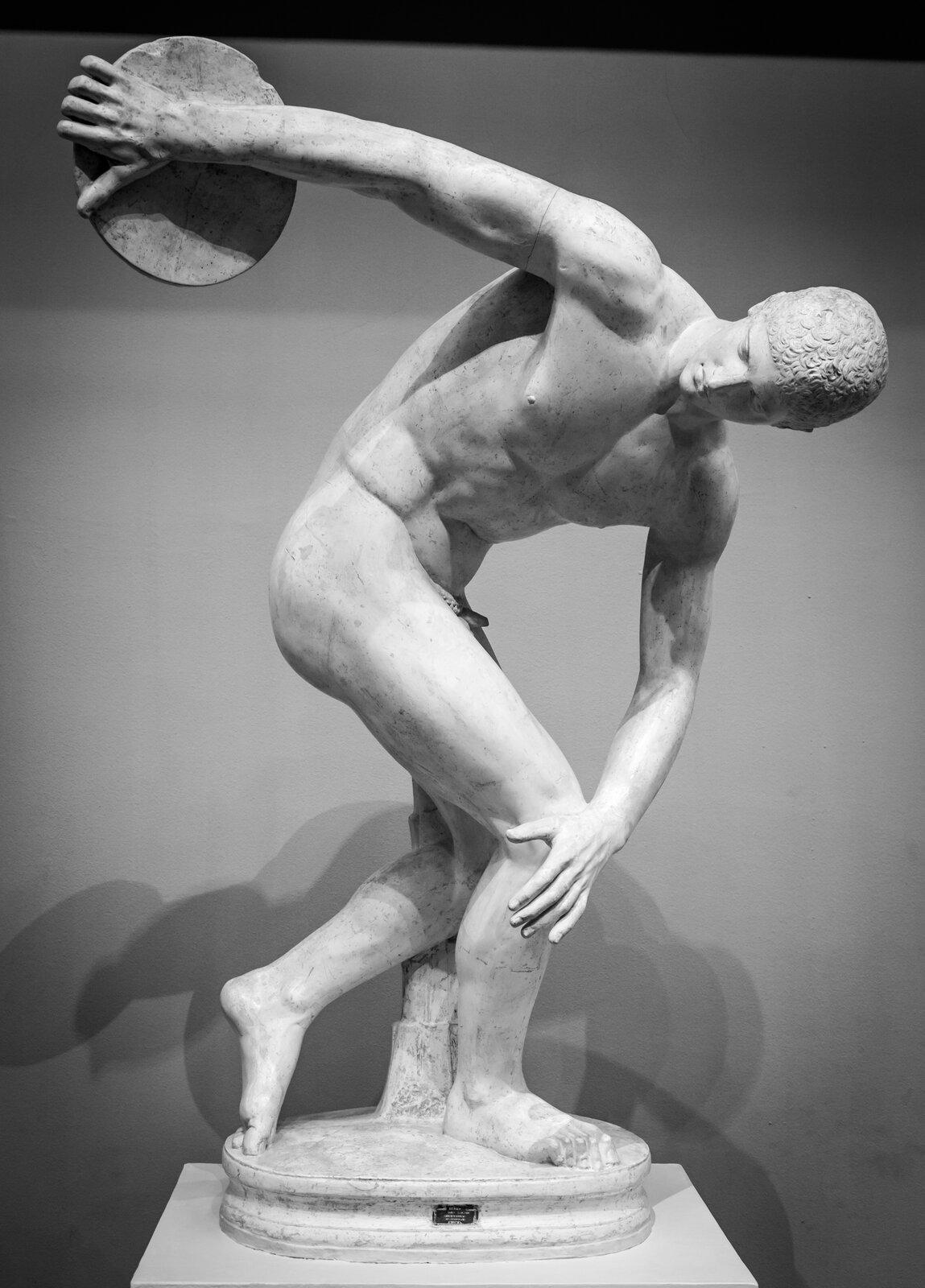"""Ilustracja przedstawia rzeźbę """"Dyskobol"""" Myron zVw. p.n.e. Jest to postać nagiego, umięśnionego mężczyzny tuż przed wyrzuceniem dysku. Ramiona są ułożone wtaki sposób, że wydaje się jakby tworzyły część okręgu. Jest pochylony, zugiętymi lekko kolanami iwprawej ręce trzyma dysk. Lewa ręka położona jest na kolanie. Prawa stopa stoi oparta wcałości na ziemi, alewa oparta jest tylko na czubkach palców. Na twarzy nie widać emocji, ajedynie skupienie. Postać ukazana jest wpełni realistycznie, oddaje naturalny ruch."""