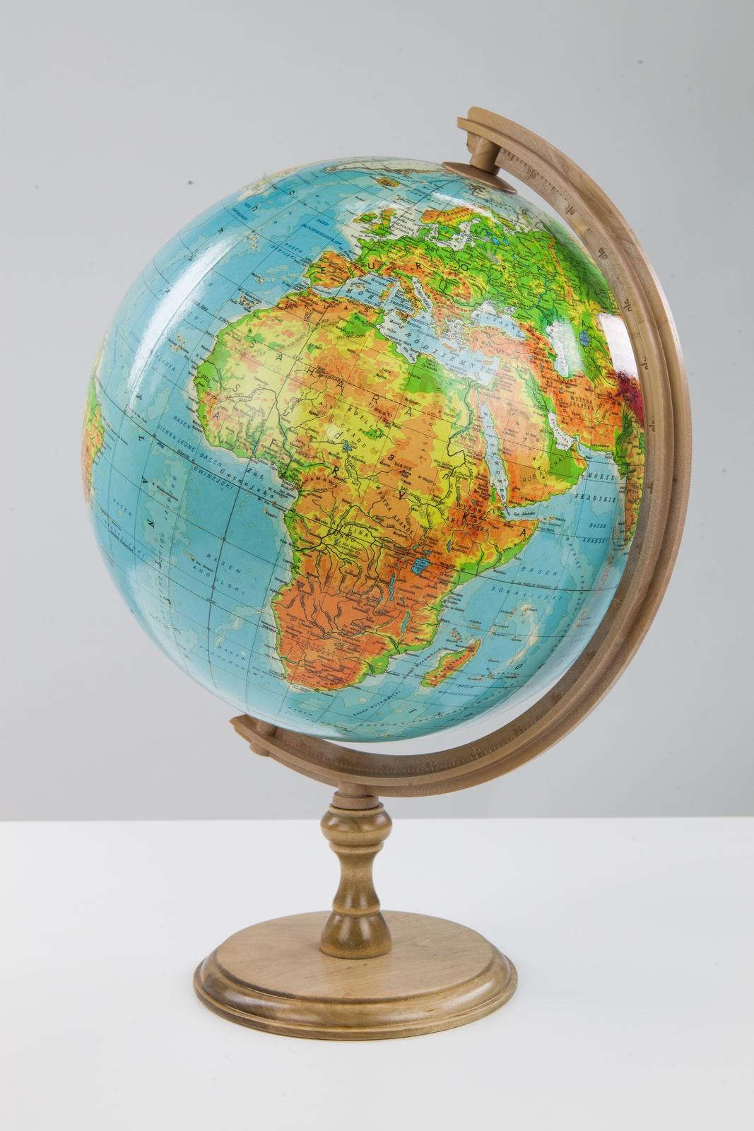 Fotografia przedstawia globus. Pomniejszony model Ziemi wpostaci kuli umieszczony jest na osi ustawionej pod kątem, przechodzącej przez jego środek iprzez dwa punkty na jego powierzchni: biegun północny ibiegun południowy.