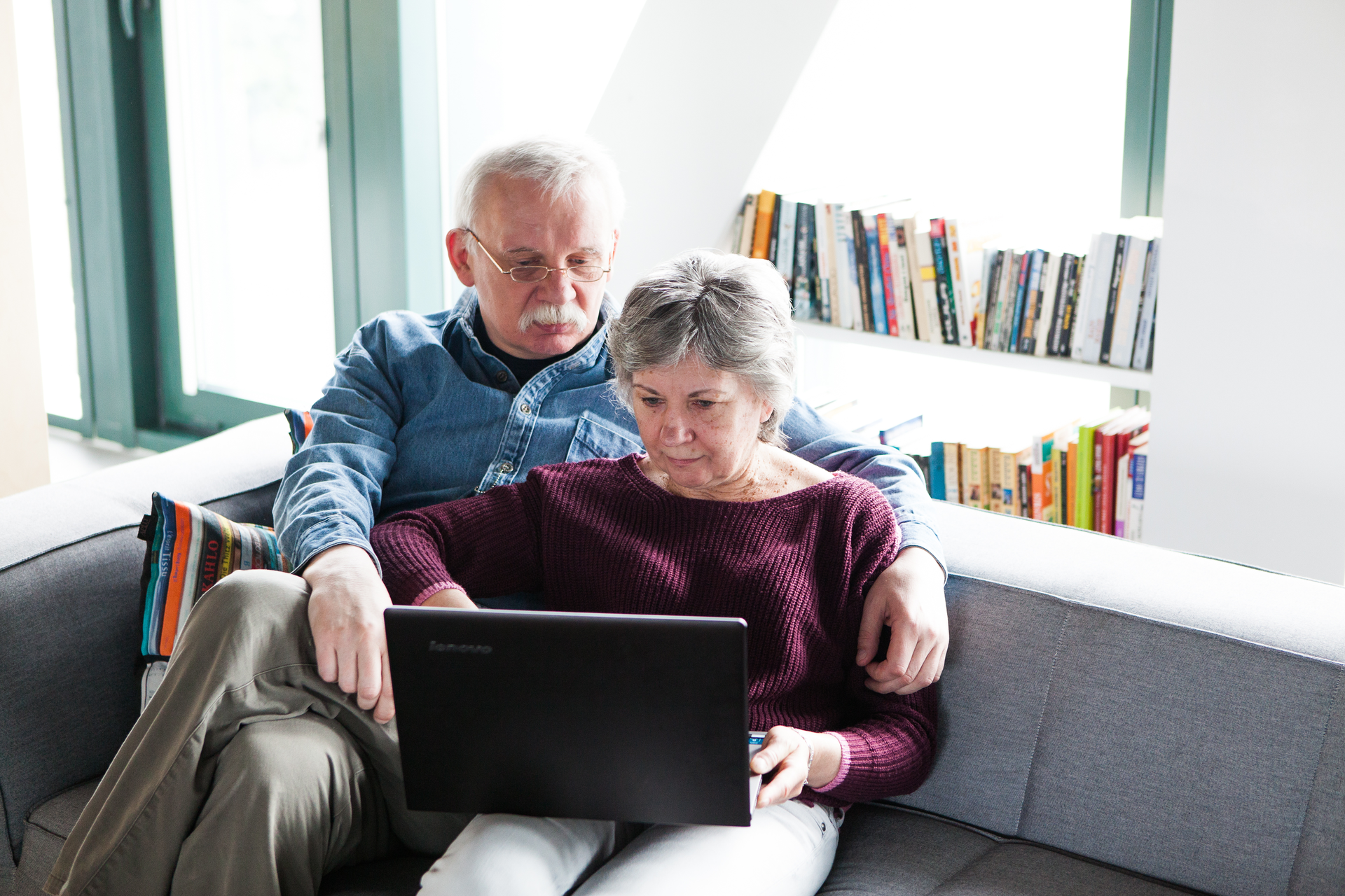Fotografia przedstawia parę ludzi wwieku około 65 lat, siedzących razem na kanapie przy komputerze. Za nimi półki zksiążkami. Okres starości pozwala oddać się swoim zainteresowaniom.