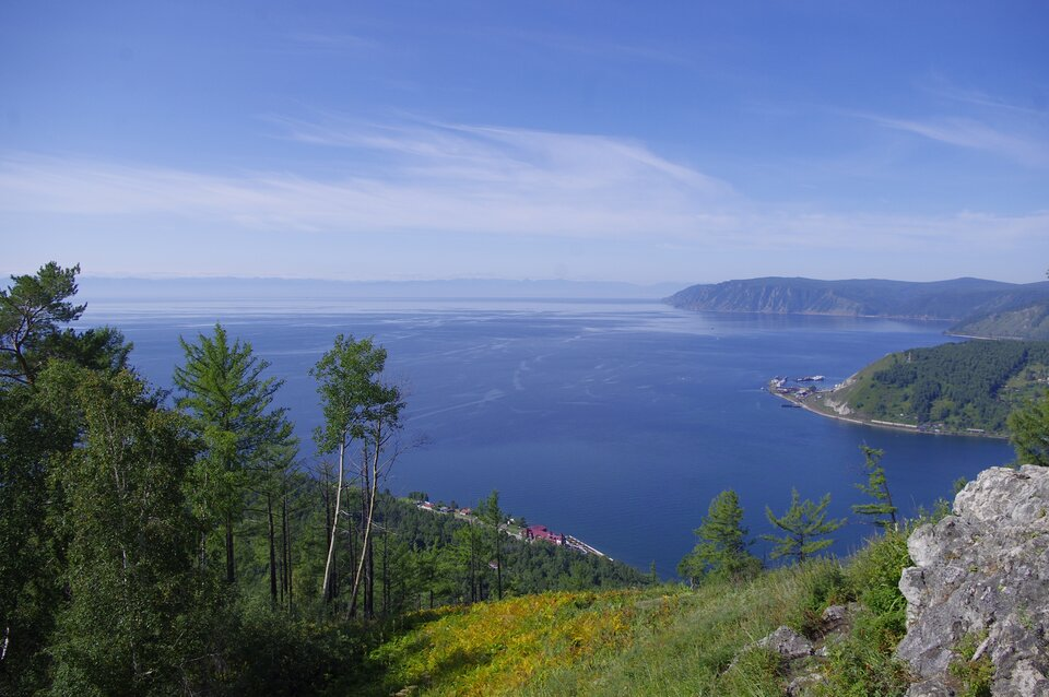 Widok na duże jezioro. Ledwo widoczny drugi brzeg. Brzegi wysokie. Wdole zabudowania. Lasy.