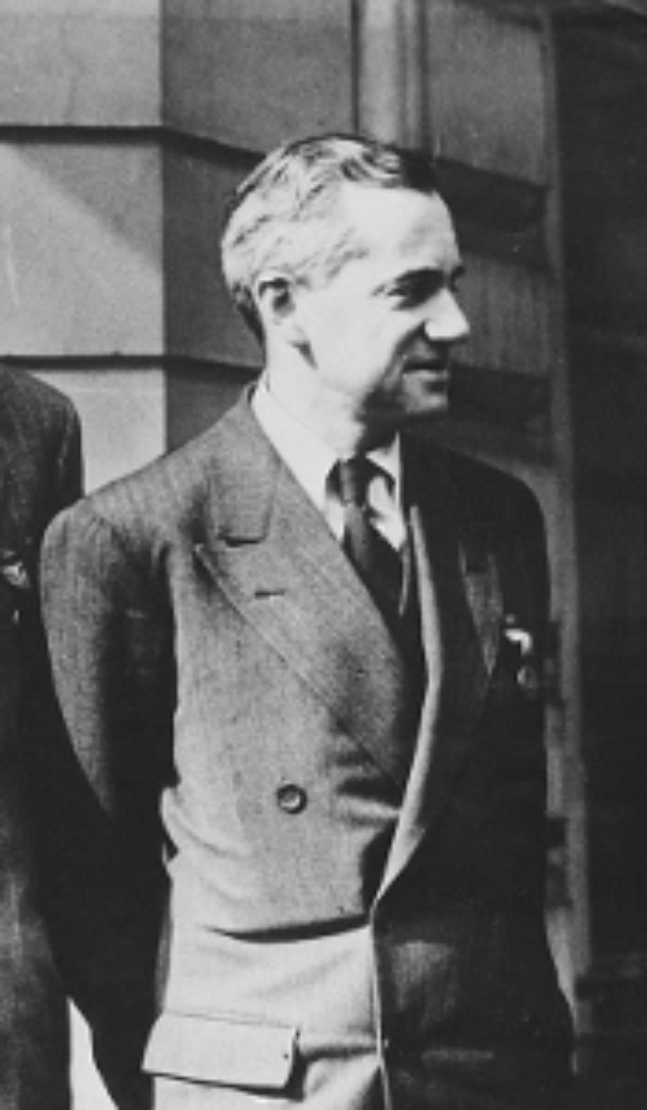 Zdjęcie przedstawia Otto Firscha. Fotografia czarno-biała. Na zdjęciu mężczyzna wwieku ok. 45 lat, szczupły. Zwrócony wbok, widoczny prawy profil. Czoło wysokie, włosy siwiejące. Nos duży. Mężczyzna delikatnie się uśmiecha. Uszy proporcjonalne, przylegające. Mężczyzna jest ubrany wtrzyczęściowy garnitur wprążki, białą koszulę oraz ciemny krawat.