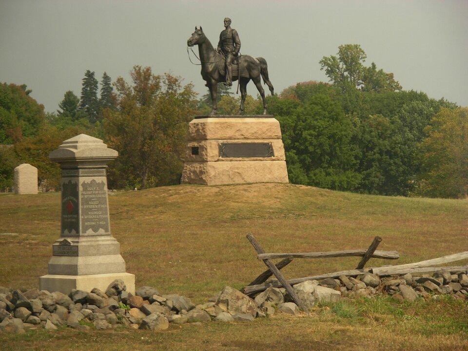 Na zdjęciu pomnik mężczyzny na koniu stoi na kamiennym postumencie. Obok kamienny słup znapisami. Zprzodu sterta kamieni.