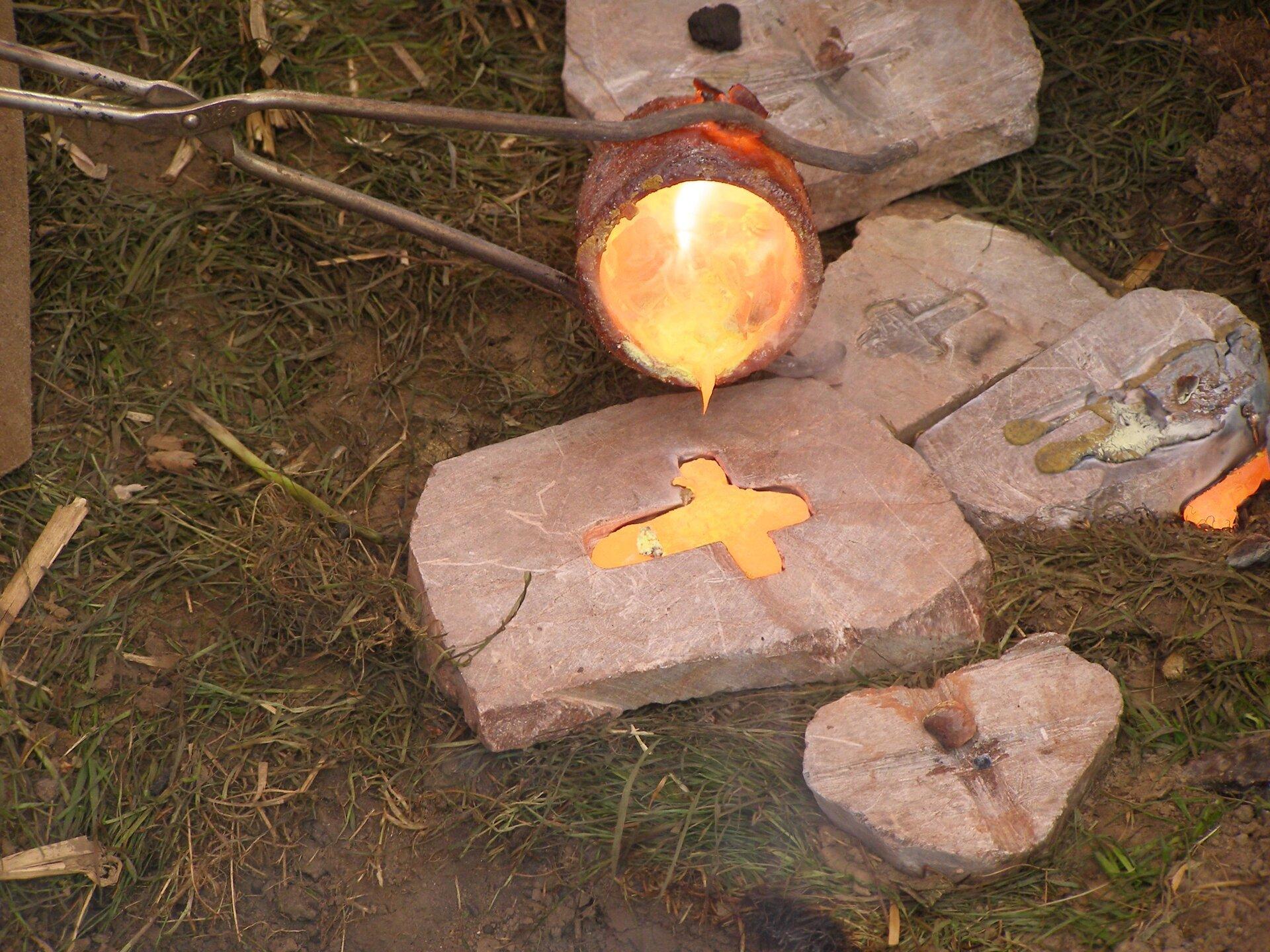 Zdjęcie przedstawia odlewanie przedmiotu zbrązu dawnymi metodami. Na obrośniętej trawą ziemi leży wycięta wkamieniu forma wkształcie krzyżyka, do której ztrzymanego wdługich szczypcach małego tygla nalewany jest płynny metal. Zarówno zawartość formy, jak itygla jarzą się czerwonawym blaskiem.