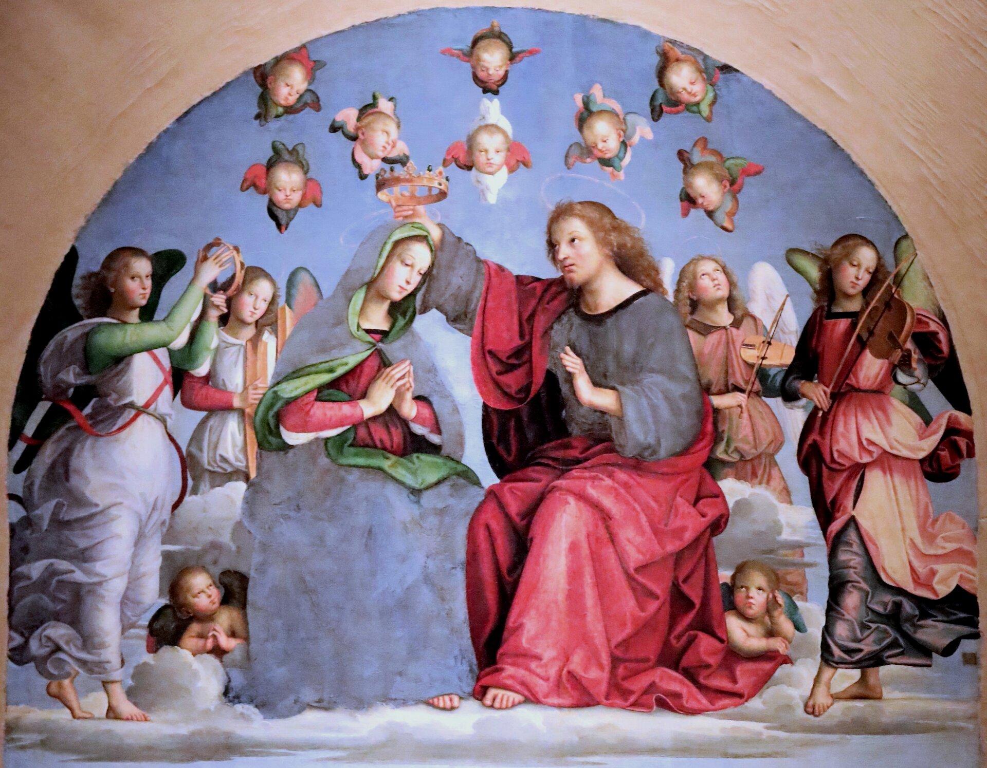 """Ilustracja interaktywna przedstawia temperę """"Koronacja Matki Bożej"""" autorstwa Rafaela Santi. Zamknięta włuku kompozycja ukazuje siedzące postacie Chrystusa iMatki Bożej wśród aniołów. Młody mężczyzna ojasnych, długich włosach, ubrany wszarą szatę, okrytą czerwonym płaszczem wwyciągniętej nad głową Marii dłoni trzyma koronę. Kobieta, odelikatnych rysach twarzy izłożonych do modlitwy dłoniach, schyla głowę wkierunku Jezusa. Matka Boża ubrana jest wczerwoną suknię, którą szczelnie okrywa wraz zwłosami szary, podbity zielenią płaszcz. Na około pary artysta umieścił grających na instrumentach aniołów. Skrzydlate postacie ubrane są wpowłóczyste, przypasane wtalii, różnobarwne stroje. Przy nogach Marii iJezusa siedzą małe, skrzydlate putta. Zjasno-niebieskiego nieba wychylają się głowy małych aniołków. Namalowane postacie unoszą się na jasnych obłoczkach."""