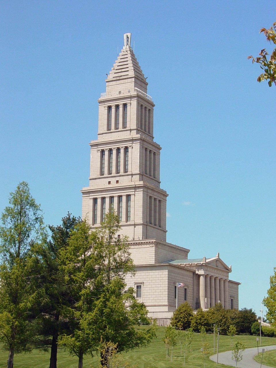 GeorgeWashington Masonic National Memorial – Narodowy Pomnik Wolnomularski poświęcony Jerzemu Waszyngtonowi wAlexsandrii wstanie Wirginia nieopodal stołecznego Waszyngtonu. Pomnik powstał wlatach 1823-1932. Prezentowany budynek główny ma wiele znaczeń inawiązań symbolicznych – np. portyk wejściowy przypomina Partenon, kolejne kondygnacje zbudowane zostały wg kolejnych porządków greckich: doryckiego, jońskiego, korynckiego, całość zwieńczono czymś, co przypomina piramidę, ajednocześniejest nawiązaniem do latarni morskiej stojącej wporcie Aleksandrii na wyspie Faros (jeden zcudów świata antycznego). Jedno zpięter stanowi muzeum poświęcone Jerzemu Waszyngtonowi, który też był członkiem loży masońskiej. GeorgeWashington Masonic National Memorial – Narodowy Pomnik Wolnomularski poświęcony Jerzemu Waszyngtonowi wAlexsandrii wstanie Wirginia nieopodal stołecznego Waszyngtonu. Pomnik powstał wlatach 1823-1932. Prezentowany budynek główny ma wiele znaczeń inawiązań symbolicznych – np. portyk wejściowy przypomina Partenon, kolejne kondygnacje zbudowane zostały wg kolejnych porządków greckich: doryckiego, jońskiego, korynckiego, całość zwieńczono czymś, co przypomina piramidę, ajednocześniejest nawiązaniem do latarni morskiej stojącej wporcie Aleksandrii na wyspie Faros (jeden zcudów świata antycznego). Jedno zpięter stanowi muzeum poświęcone Jerzemu Waszyngtonowi, który też był członkiem loży masońskiej. Źródło: Ben Schumin, Wikimedia Commons, licencja: CC BY-SA 2.5.