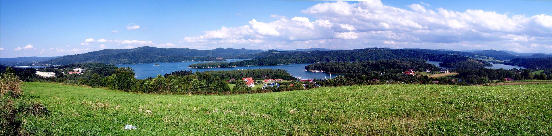 Galeria prezentuje fotografie sztucznych zbiorników wodnych. Fotografia prezentuje Jezioro Solińskie – zbiornik zaporowy powstały na rzece San. Na pierwszym planie widoczny porośnięty trawą pagórek. Wdole rozległe Jezioro Solińskie zlicznymi zielonymi wyspami.