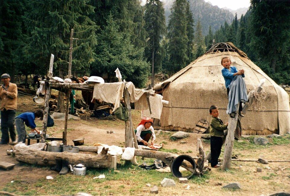 Na zdjęciu rodzina przed jurtą, dzieci bawią się, kobieta gotuje, ktoś zmywa naczynia wmisce. Na kijach suszy się pranie. Wtle las.