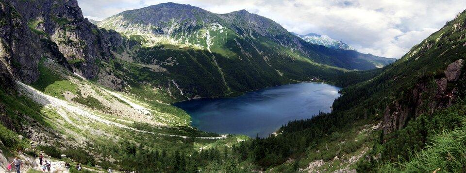 Na zdjęciu wysokie góry, szczyty skaliste, wdolinie jezioro oregularnym kształcie.
