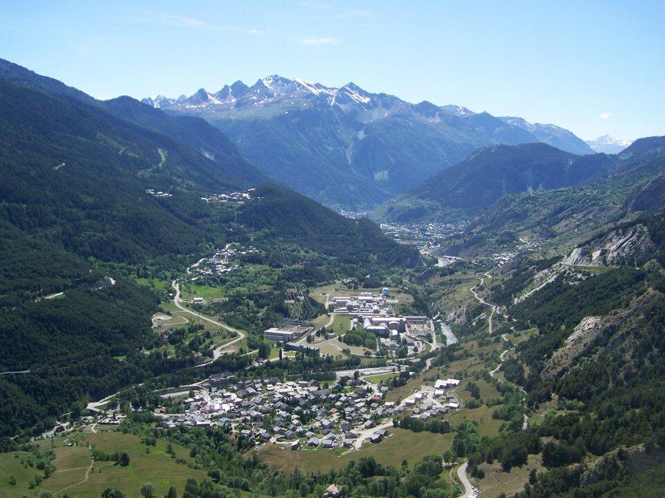 Na zdjęciu silnie pofałdowany teren górski, ośnieżone szczyty, wcentrum kotlina, zabudowania mieszkalne.
