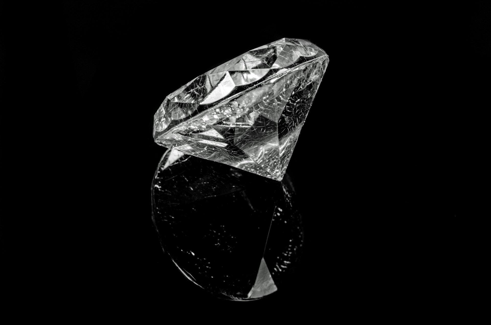 Zdjęcie przedstawia oszlifowany diament, czyli brylant leżący na czarnym tle odbijającym wpewnym stopniu obraz jasnych partii kamienia.