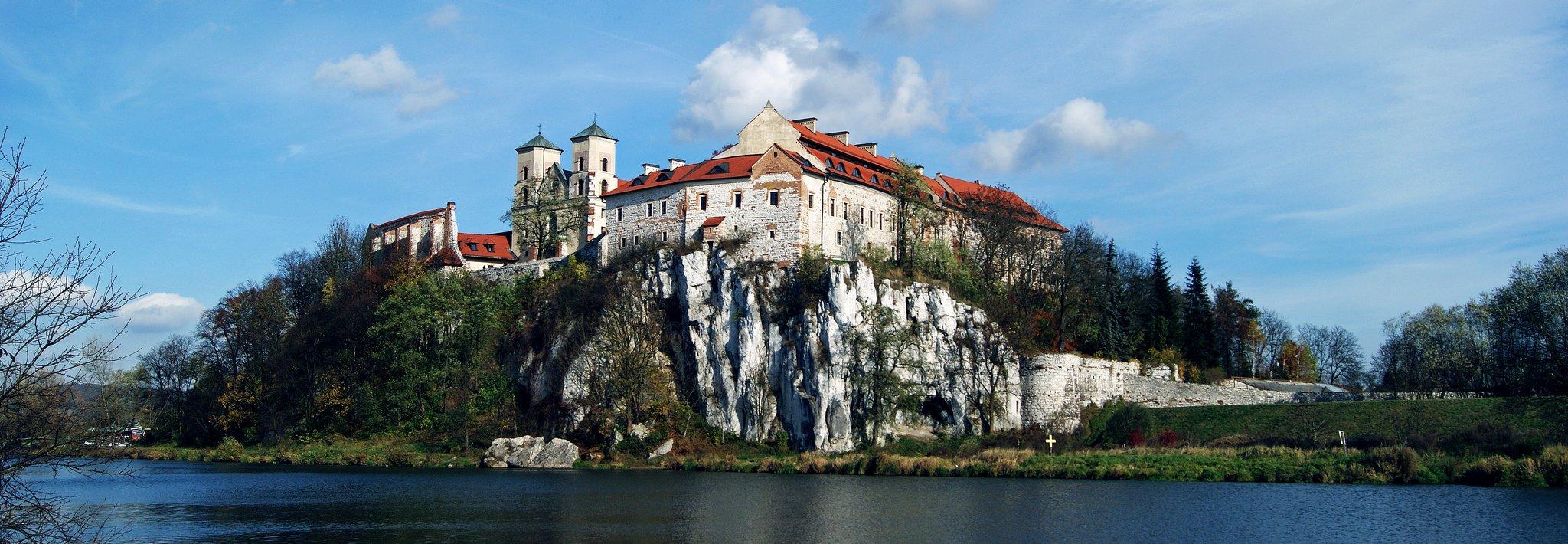 Zabudowania zbiałego kamienia pokryte czerwonym dachem na skalnej skarpie nad rzeką. Budynki otoczone są murami obronnymi, jednym zbudynków jest kościół odwóch wieżach.