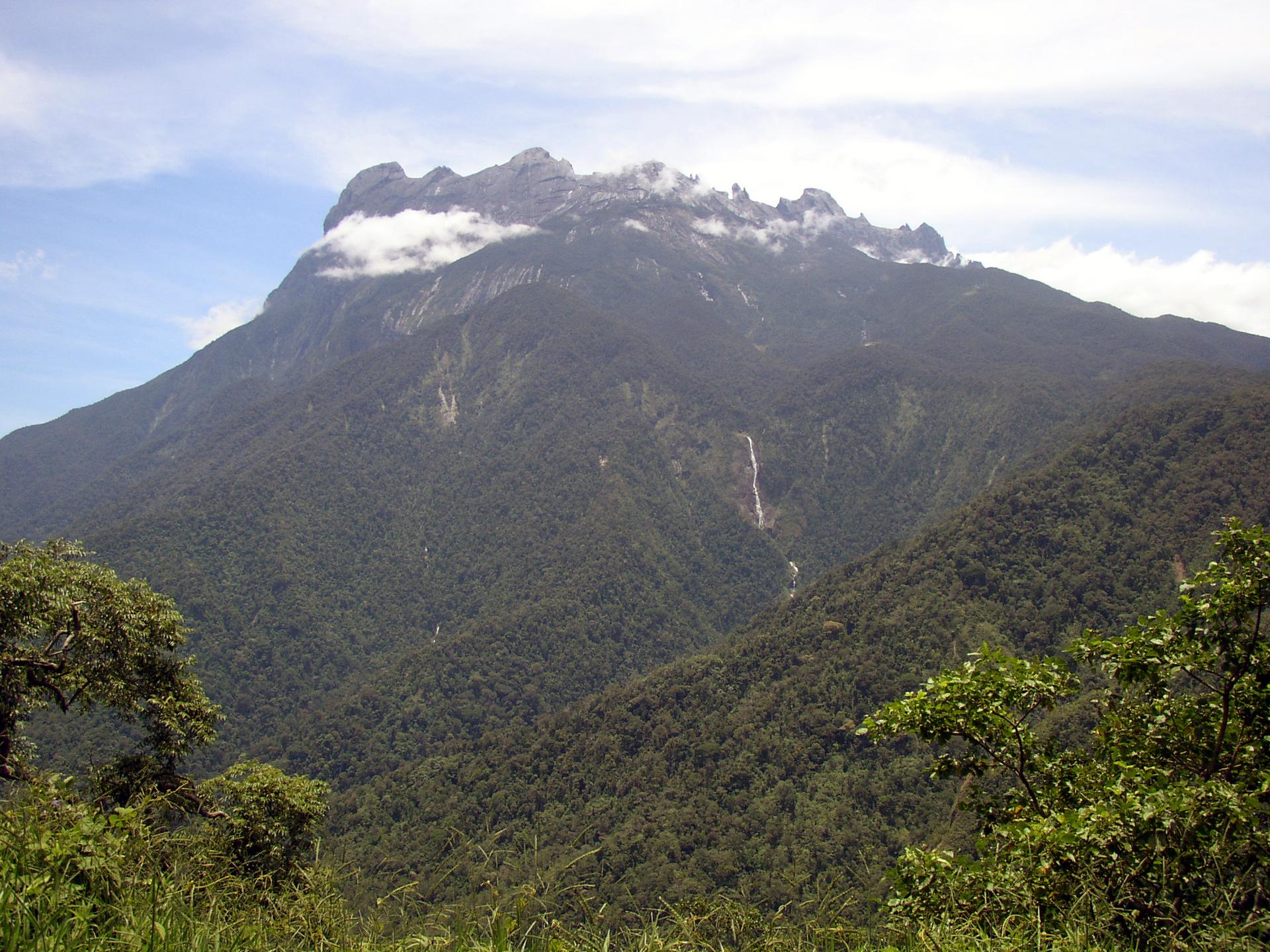 Na zdjęciu wysoki skalisty szczyt górski. Poniżej zalesione stoki.