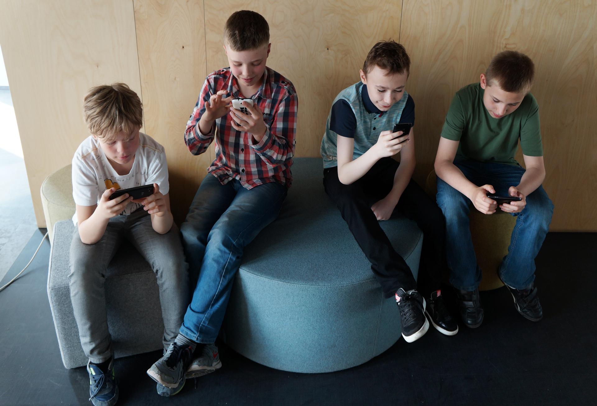Fotografia przestawia widzianą zgóry grupę czterech chłopców. Mają około 10-12 lat. Siedzą na pufach. Każdy znich patrzy wekran swojego telefonu, odczytuje lub wysyła wiadomości.