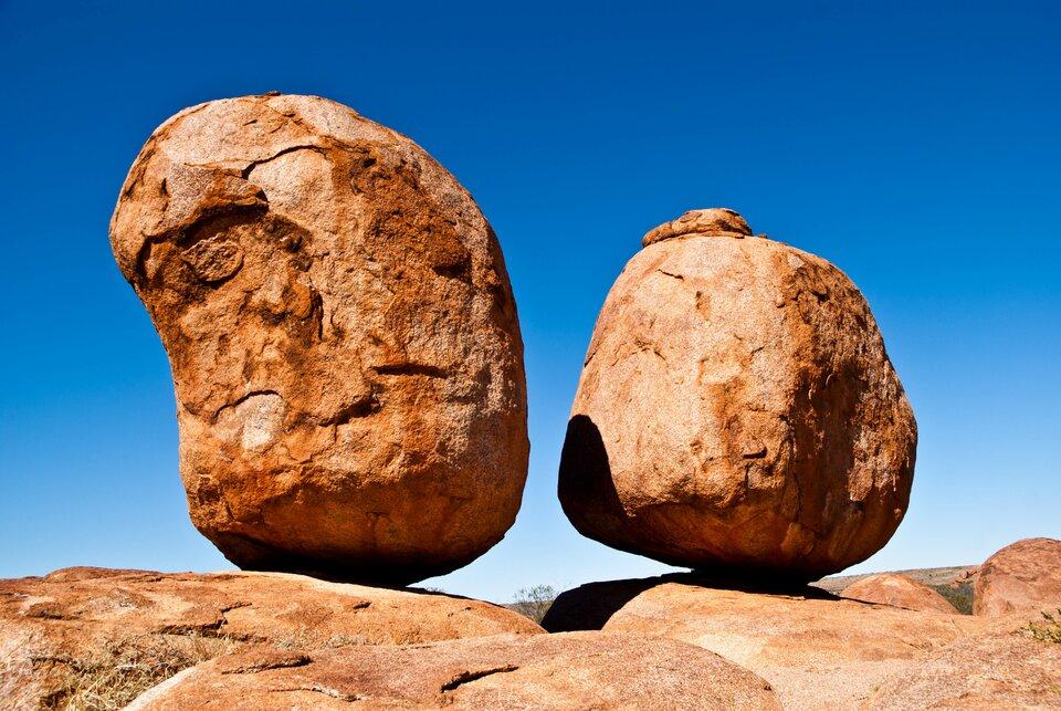 Na zdjęciu dwie owalne skały stojące na powierzchni skalnej. Skała zlewej strony nieco większa. Bloki skalne mają kolor ceglasty. Wtle niebieskie niebo.