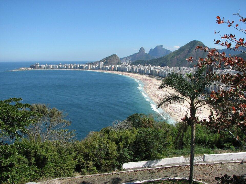 Na zdjęciu widok na brzeg morza, piaszczystą plażę, wtle nowoczesne zabudowania, dalej wysokie góry.